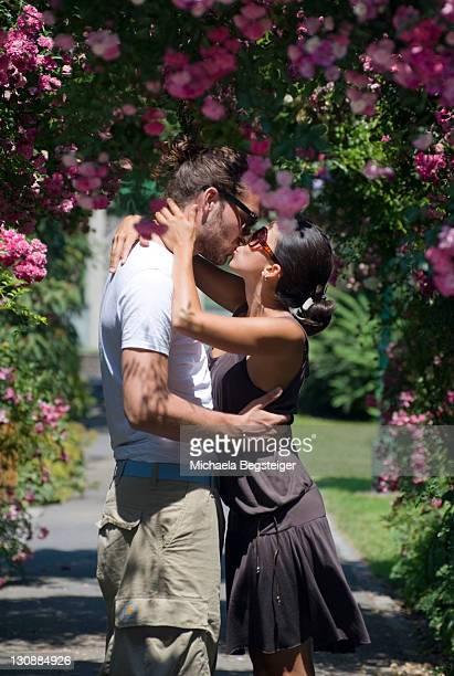Young love couple kissing under a rosebush