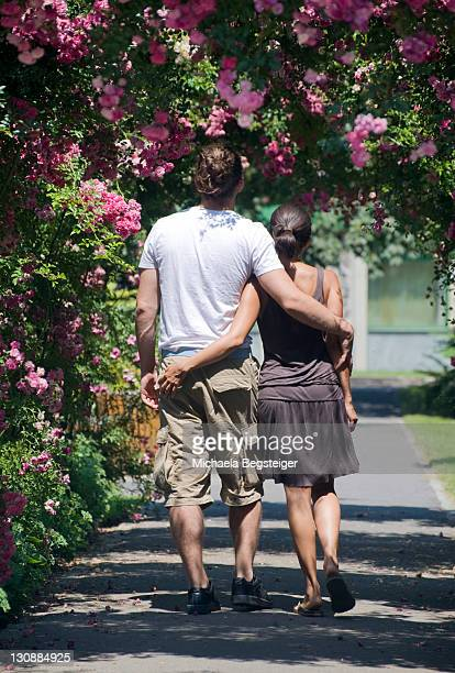 Young love couple strolling under a rosebush