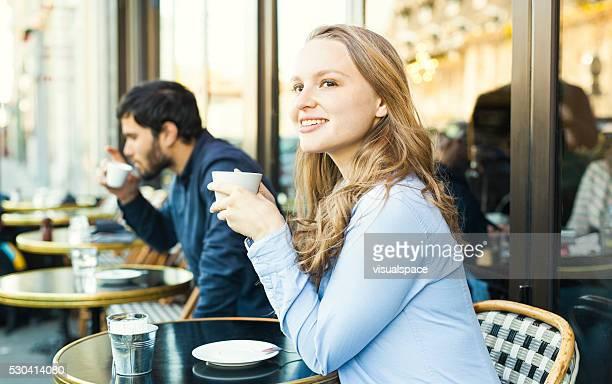 Belle jeune femme ayant une pause-café dans la cafétéria avec terrasse