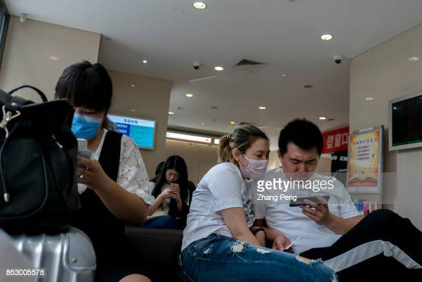 Young lovers are watching video on mobile phone in a bank In the first half of 2017 the Chinese users of mobile music video games and reading grew by...