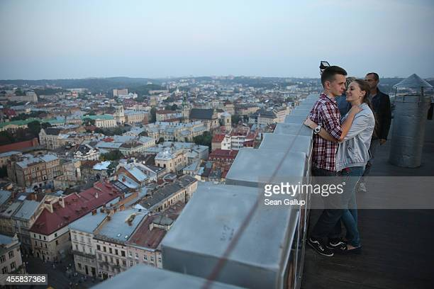 Young lovers cuddle on the tower terrace on Rynok Square on September 15, 2014 in Lviv, Ukraine. Lviv, which is located in western Ukraine near the...