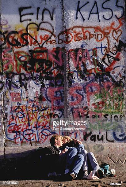 Young lovers kiss at the Berlin Wall on the morning that the first section of the Berlin Wall was pulled down