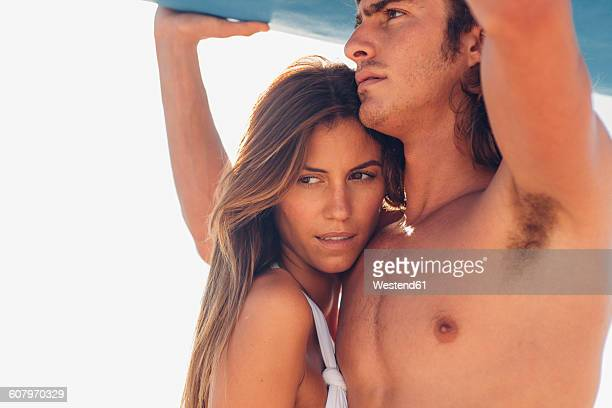 Young lovers together under their surfboard on a sunny day at the beach