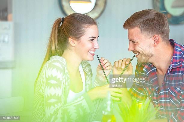若いカップルで飲むのが大好きなストローからのガラス
