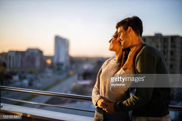 jovem casal amoroso curtindo seu tempo em um terraço. - sacada - fotografias e filmes do acervo