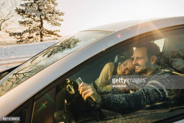 Young loving couple going on a road trip during winter day.