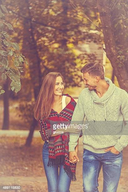 Joven amante pareja sosteniendo las manos en un paseo a través de la naturaleza