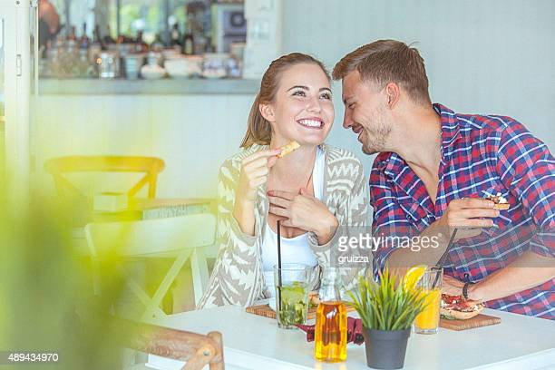 Young loving couple pleasantly chatting on a date in restaurant
