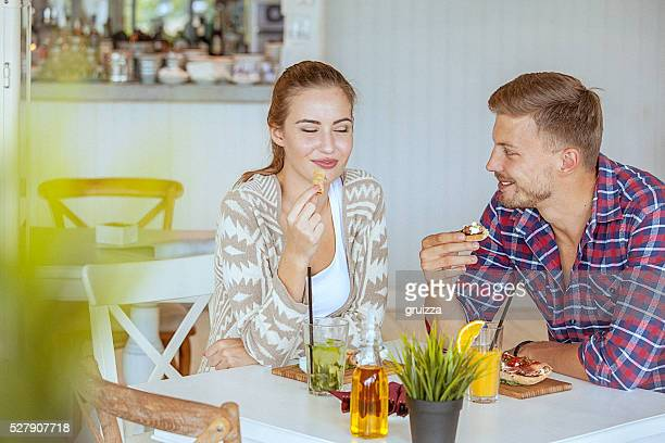 giovane coppia di innamorati piacevolmente chiacchierare su una data nel ristorante - coppia eterosessuale foto e immagini stock