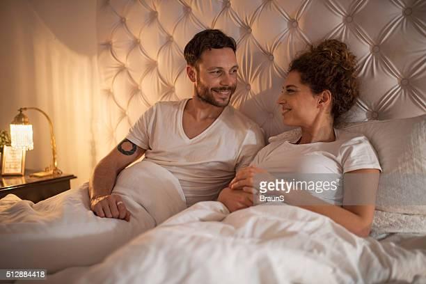 jeune couple de détente au lit et communiquent. - couple au lit photos et images de collection