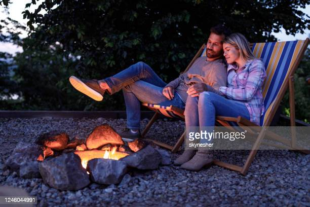 焚き火でデッキチェアでリラックスした若い愛情のあるカップル。 - 焚き火 ストックフォトと画像