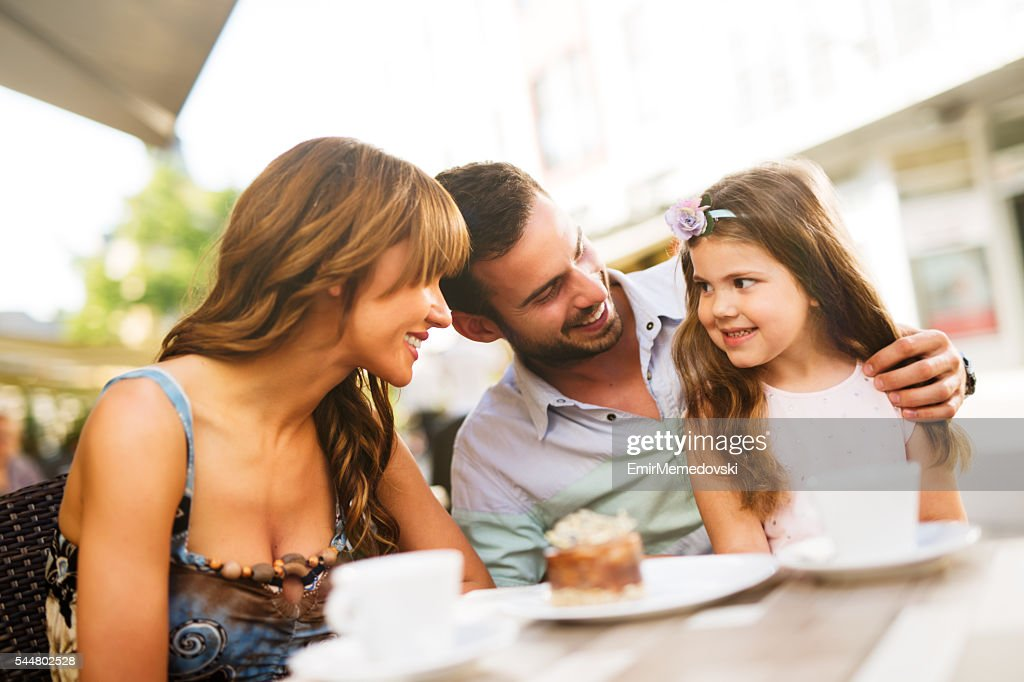 Young loving family having fun in a cafe eating cake. : Stock Photo