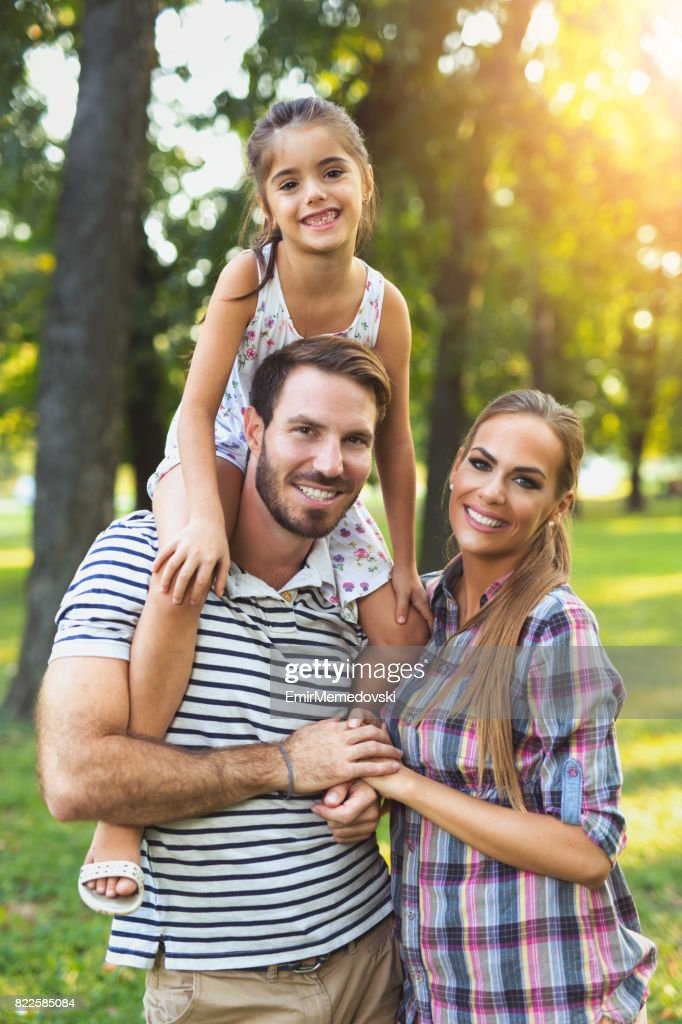 Young loving family having fun in the park. : Stock Photo