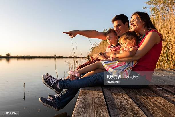 Young loving family relaxing on a pier by the lake.