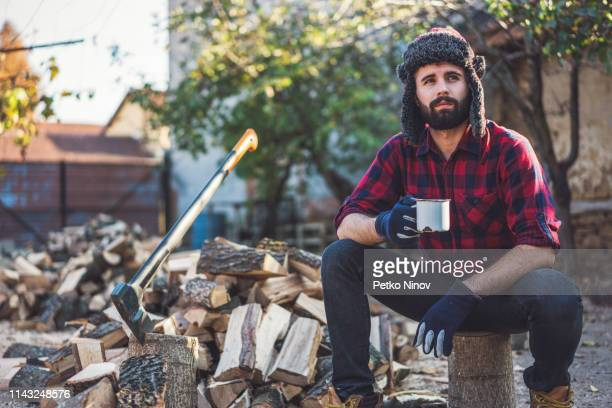 young lumberjack resting with some coffee - masculinity stock pictures, royalty-free photos & images