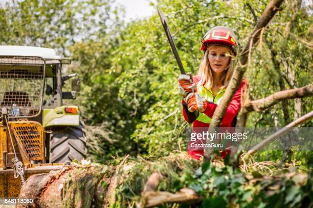 Young Lumberjack Woman Chopping a Tree Branch