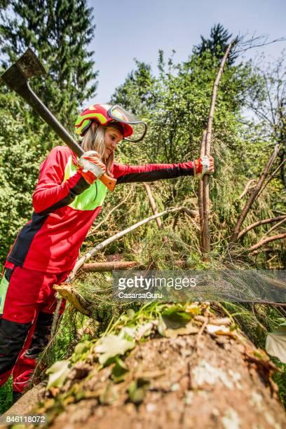 Junge Holzfäller Frau hacken einen Ast