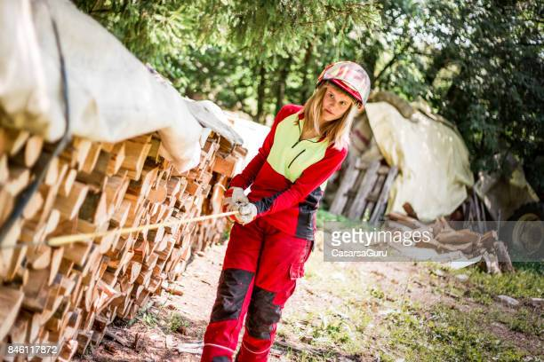 Young Lumberjack Woman Measuring the Stack of Timbers