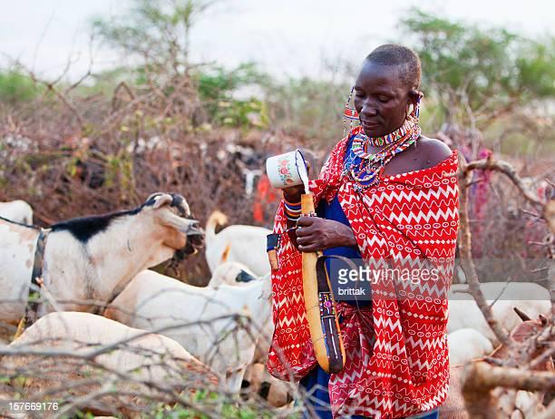 Young Maasai woman pouring goats milk into calabash