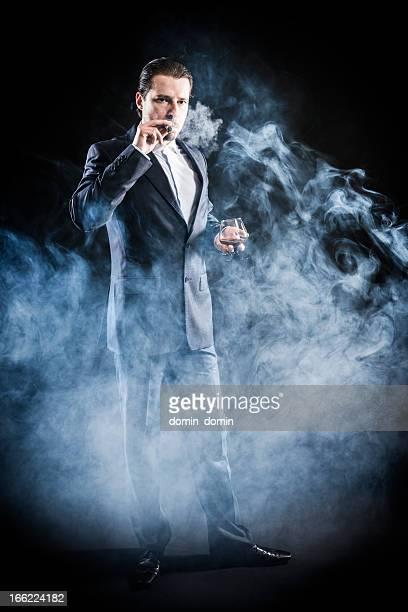 若い mafioso スーツで喫煙葉巻、飲みのブランデー、まとめ髪