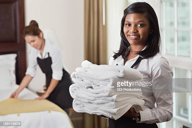 Young maid with towels in hotel room