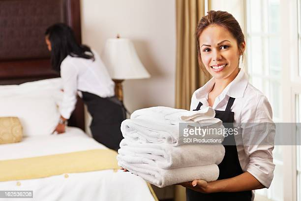 young maids cleaning and preparing room for hotel guests - commercial cleaning stock photos and pictures