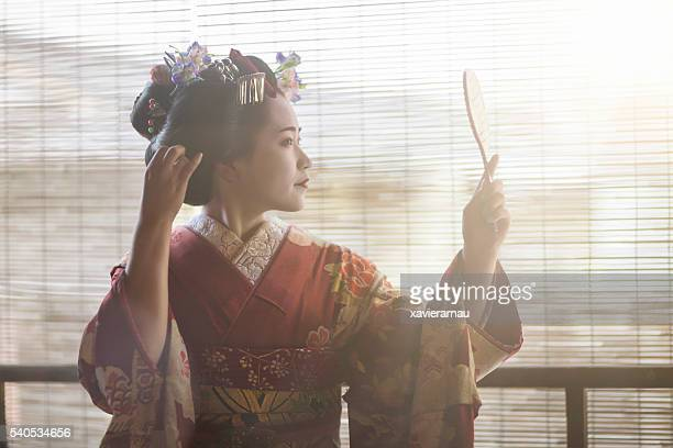 Young Maiko looking herself at a hand mirror