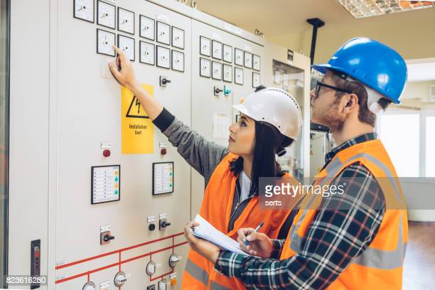 Young maintenance engineer team working at energy control room