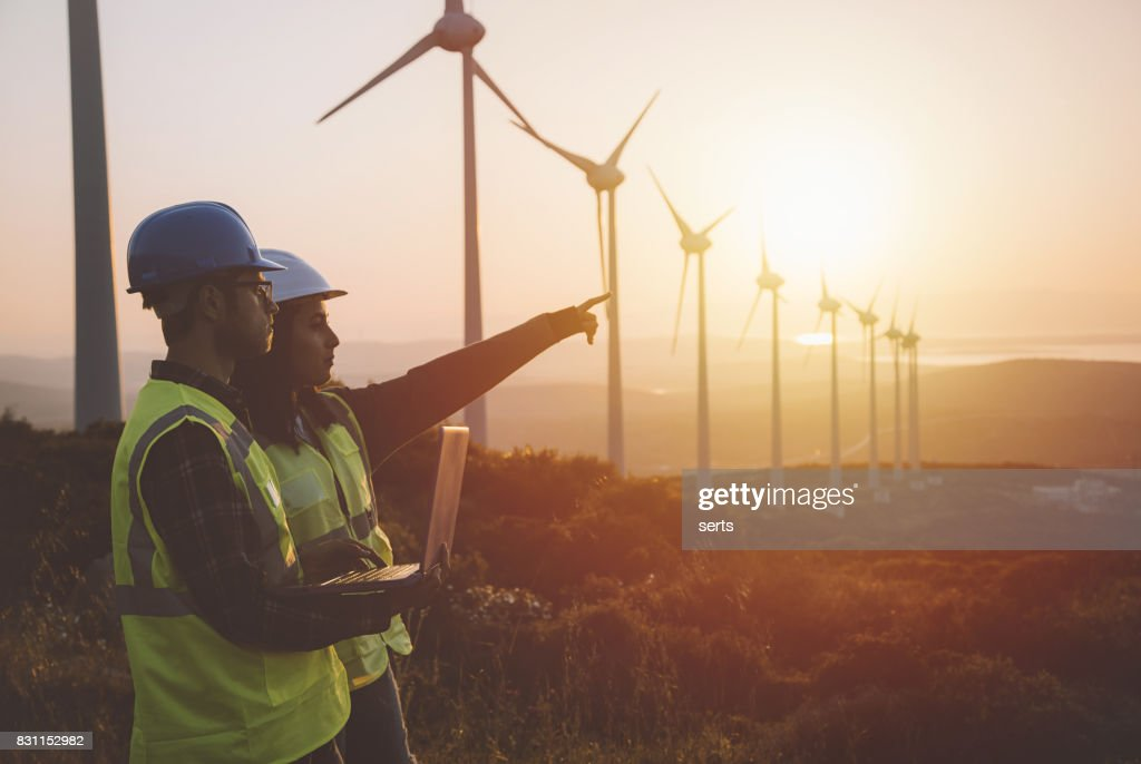Young maintenance engineer team working in wind turbine farm at sunset : Stock Photo