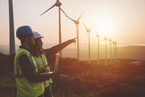 Young maintenance engineer team working in wind turbine farm at sunset 831152982