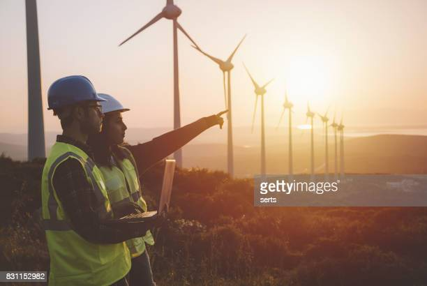 Young maintenance engineer team working in wind turbine farm at sunset
