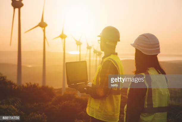 young maintenance engineer team working in wind turbine farm at sunset - power occupation stock photos and pictures