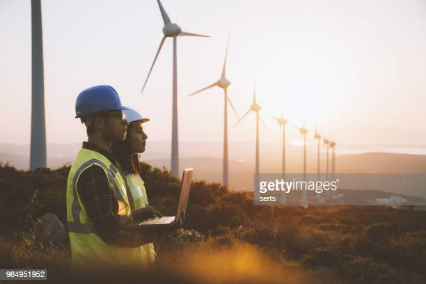young maintenance engineer team working in wind turbine farm at sunset - fuel and power generation stock pictures, royalty-free photos & images
