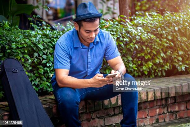 Young Malay man sitting outdoor with his smart phone
