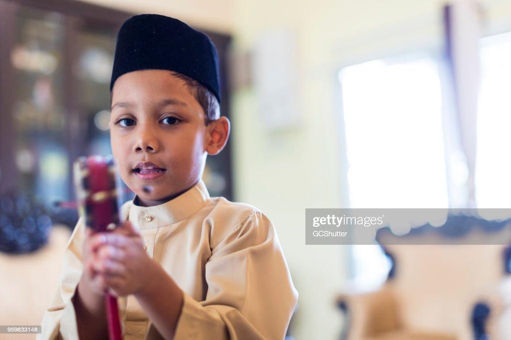 Malaysische junge in traditioneller Kleidung mit seinem Spielzeug spielen. : Stock-Foto
