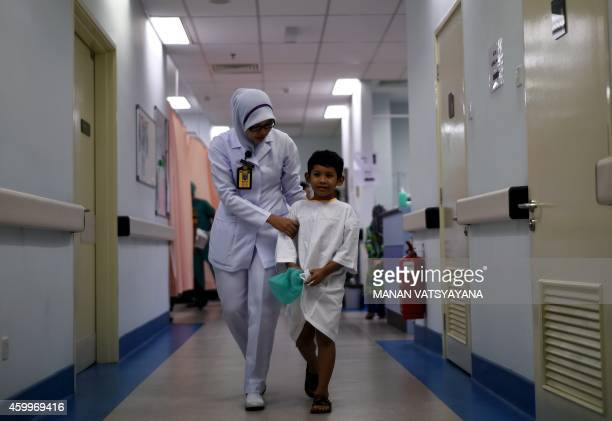 Young Malaysian boy is assisted by a nurse after a circumcision ceremony at the Tuanku Mizan Army hospital in Kuala Lumpur on December 5, 2014. 112...
