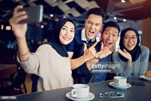 young malaysian couples are drinking coffee and taking selfie/make video call in the cafe - malaysian culture stock pictures, royalty-free photos & images