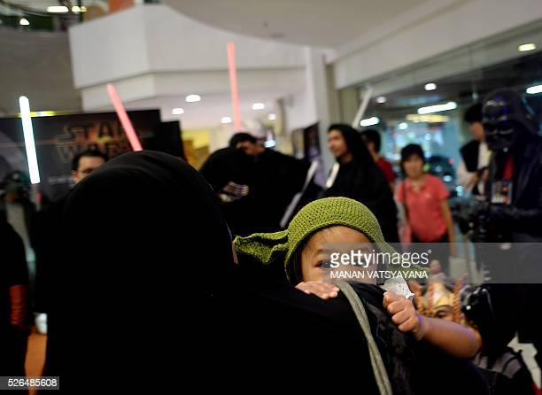A young Malaysian dressed as baby Yoda clings on to her mother during an event to mark the Star Wars Day celebration in Kuala Lumpur on April 30 2016...