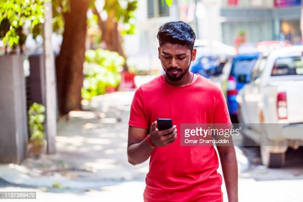 young malaysian man using smart phone while walking on the street of kuala lumpur - omar shamsuddin stock pictures, royalty-free photos & images
