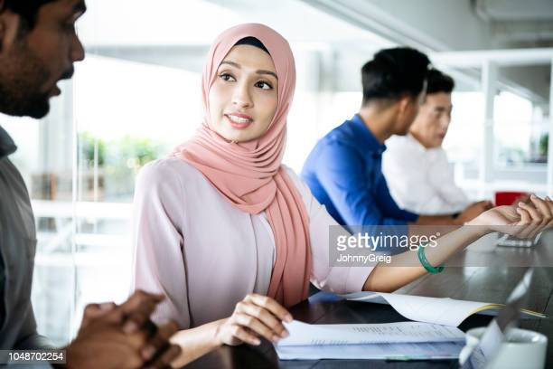 young malaysian woman listening to colleague in office - respect stock pictures, royalty-free photos & images