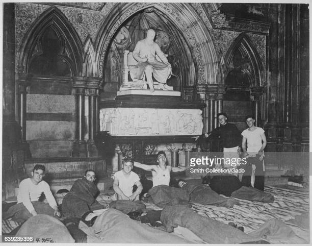 Young male American soldiers dressed in pajamas and wrapped in wool sleeping bags go to rest for the night inside the Royal Courts of Justice in...