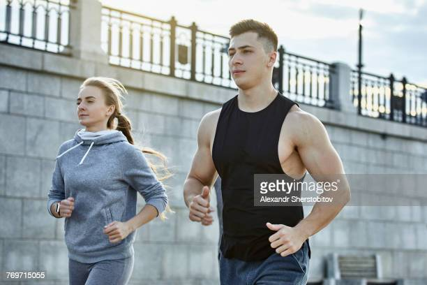 Young male and female athletes jogging against wall