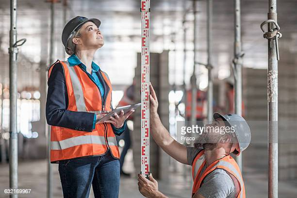 Young male and female builders measuring construction with ruler