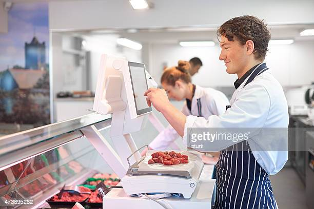 young male and female butchers working in a butcher's shop.