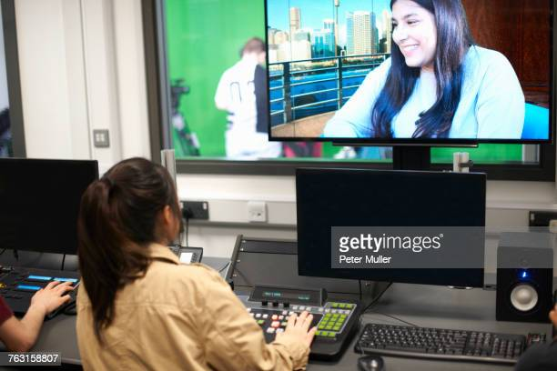 young male and female college students at mixing desk watching tv screen - post-production stock pictures, royalty-free photos & images