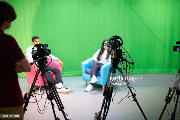 young male and female college students practicing in tv studio with green screen - chroma key fotografías e imágenes de stock