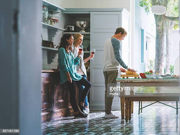 Young male and female friends socializing at home