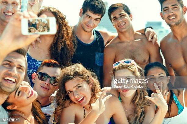 Young male and female friends taking group selfie and having fun at the beach on a sunny day