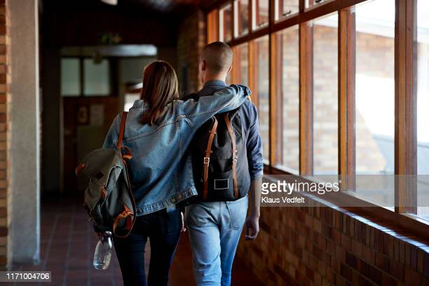 young male and female friends walking in corridor - blue jacket stock pictures, royalty-free photos & images