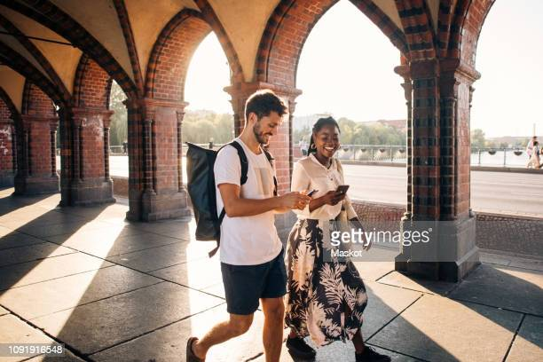 young male and female friends walking on footpath in city - city break stock pictures, royalty-free photos & images
